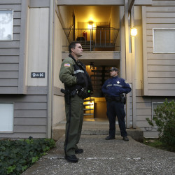 Douglas County Deputy Sheriff Greg Kennerly, left, and Oregon State Trooper Tom Willis stand guard on Oct. 2 outside the apartment building where alleged Umpqua Community College gunman Chris Harper Mercer lived with his mother in Roseburg, Ore. The Associated Press