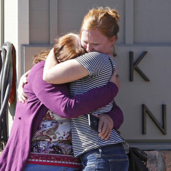 Umpqua Community College alumnus Donice Smith, left, is embraced last week after she said one of her former teachers was shot dead, near the site of the mass shooting in Roseburg, Oregon.