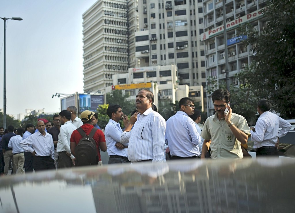 People stand on a road divider after vacating buildings during an earthquake in New Delhi, India, on Monday. (Reuters)