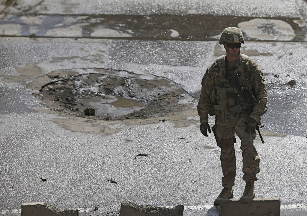 A soldier stands at the site of a suicide car bomb blast in Kabul on Sunday. A suicide car bomber targeted a convoy of troops in the Afghan capital during rush-hour traffic, flipping an armored vehicle on its side, but the number of casualties was unknown. Reuters