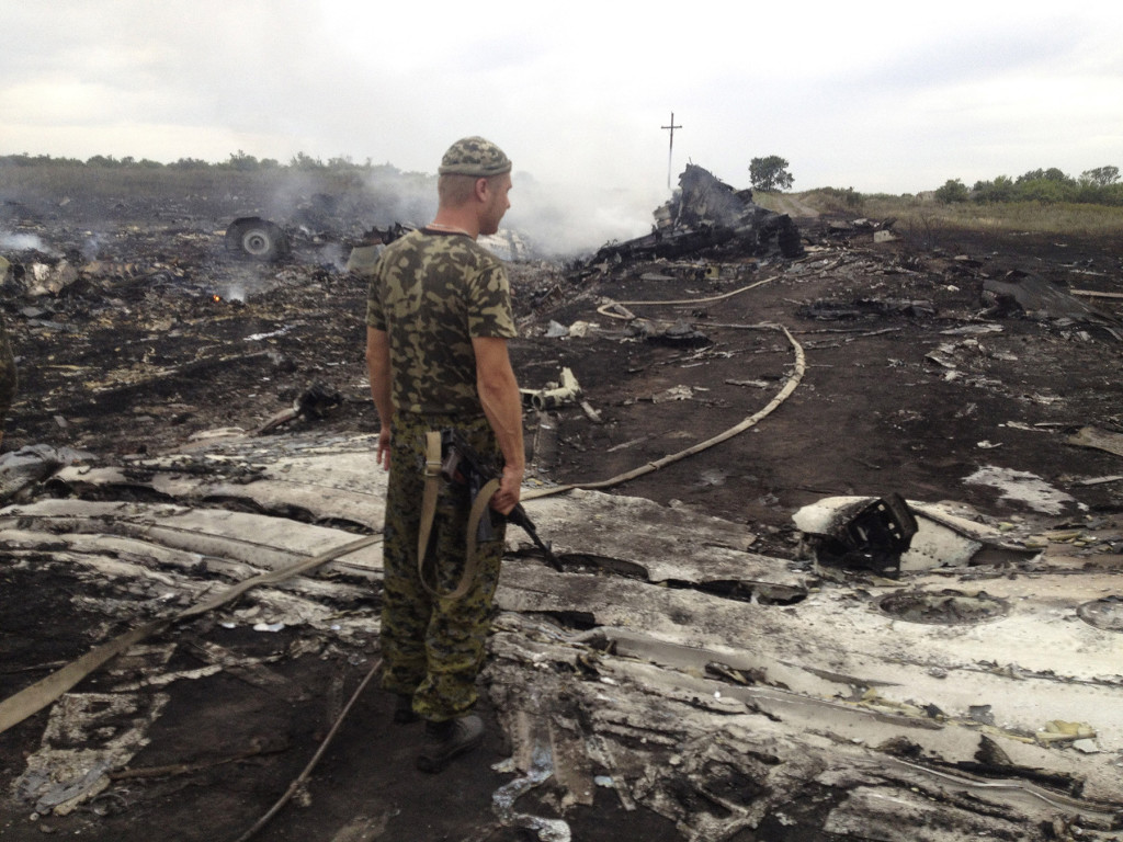 An armed pro-Russian separatist stands at a site of a Malaysia Airlines Boeing 777 plane crash in the settlement of Grabovo in the Donetsk region Thursday. Dozens of bodies were scattered around the smoldering wreckage. An emergency services rescue worker said at least 100 bodies had so far been found at the scene. Reuters