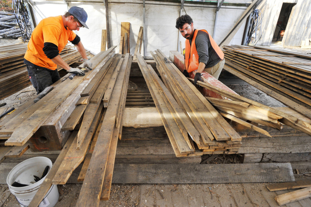 In this 2015 file photo, Travis Dame, left, of North Berwick, and Aaron Corme of Somersworth, New Hampshire, remove nails from newly acquired boards at Longleaf Lumber in Berwick. The company has supplied reclaimed wood from Maine for several Boston restaurants.