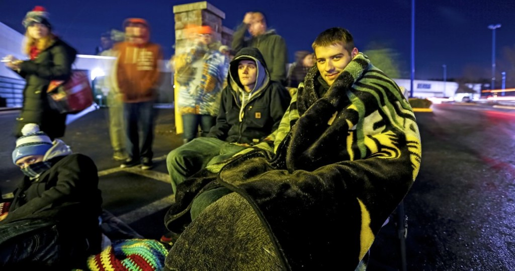 Dana Lamson, right, and Brennon Williams, of Saco, are among a long line of people waiting  to get into Best Buy at the Maine Mall before its midnight opening for Black Friday. Both had been waiting since 7 p.m. Ben McCanna/Staff Photographer
