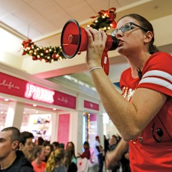 Pink employee Nicole O'Donnel uses a megaphone to corral shoppers into a long line shortly after midnight on Black Friday at the Maine Mall. Ben McCanna/Staff Photographer