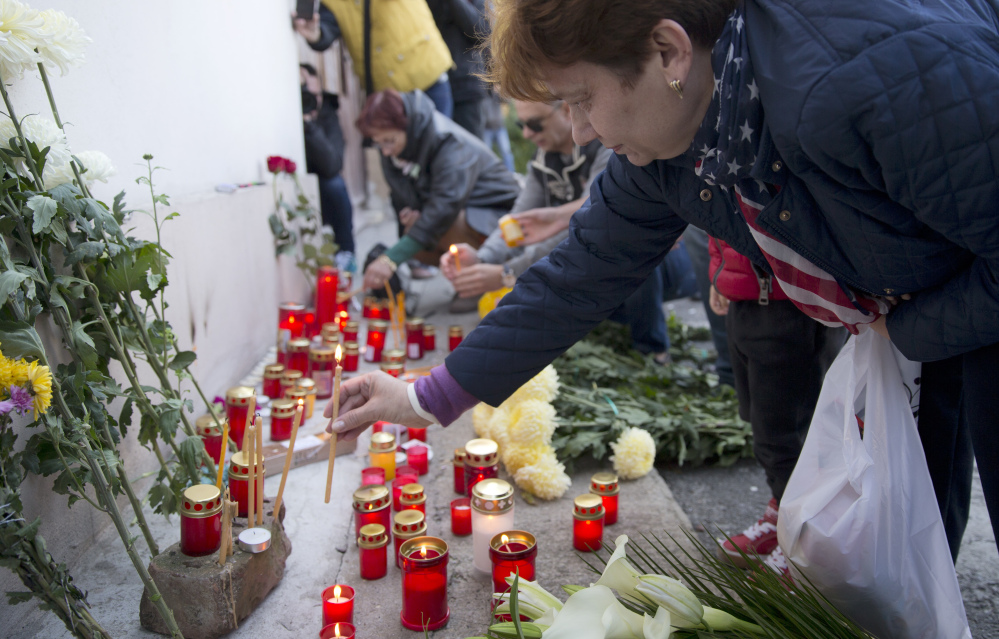 A woman lights candles outside the compound that housed the nightclub where a fire occurred in the early morning hours in Bucharest, Romania, on Saturday.