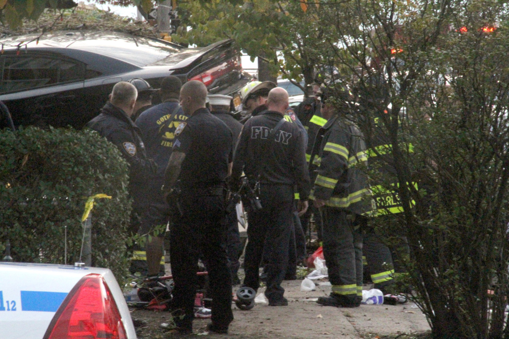 First responders examine an automobile after its driver lost control and plowed into a group of trick-or-treaters Saturday in New York.