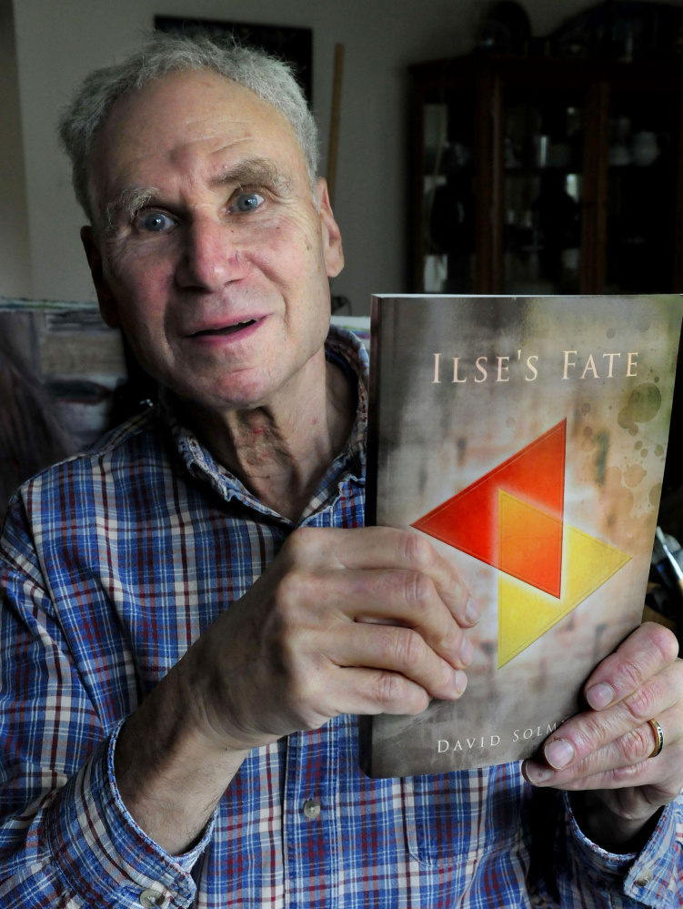 """Author David Solmitz, of Waterville, holds a copy of his latest book, """"Ilse's Fate,"""" on Sunday."""