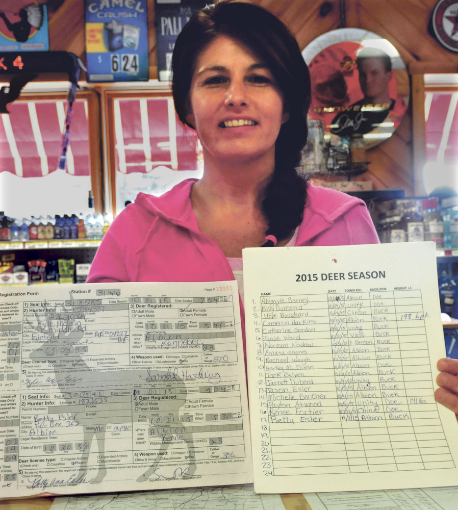 Albion Corner Store employee Pam Morneau holds a state deer registration form and a tally of the 17 deer that were tagged at the store on opening day of firearm deer season for Maine residents on Saturday.