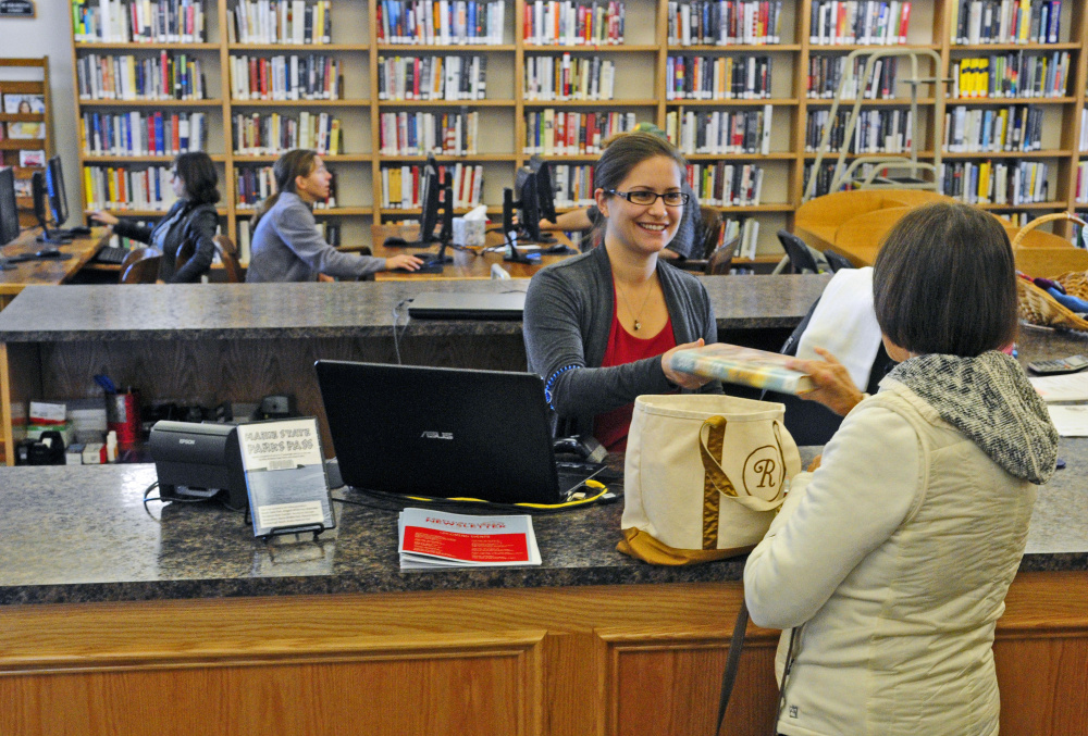 Library technician Katherine Webber, left, checks out books for Gail Ramsey on Friday at C.M. Bailey Public Library in Winthrop.