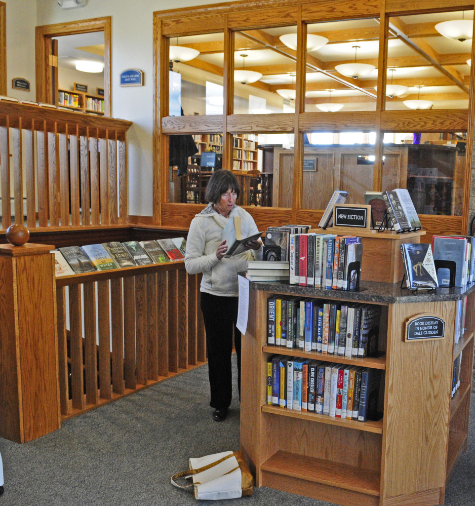 Gale Ramsey browses a shelf of new books just inside the door on Friday at C.M. Bailey Public Library in Winthrop.