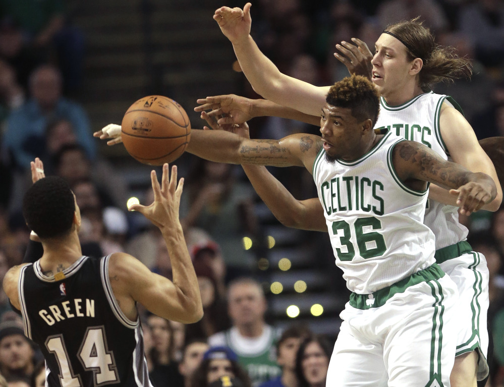 San Antonio guard Danny Green, left, battles for control of the ball with Boston guard Marcus Smart, center, and center Kelly Olynyk, right, in the second quarter Sunday in Boston.