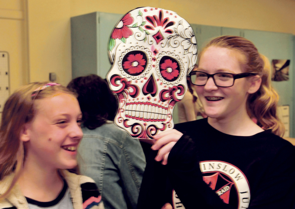 Winslow Junior High School students Katie Stevens, left, and Felicia Lessard have fun with a mask the spanish class made for Day of the Dead on Monday.