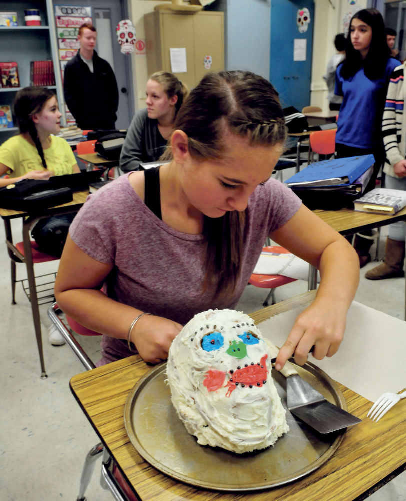 Winslow Junior High School student Savannah Joler begin to cut a cake made in the form of a skull during the Day of the Dead celebration on Monday.