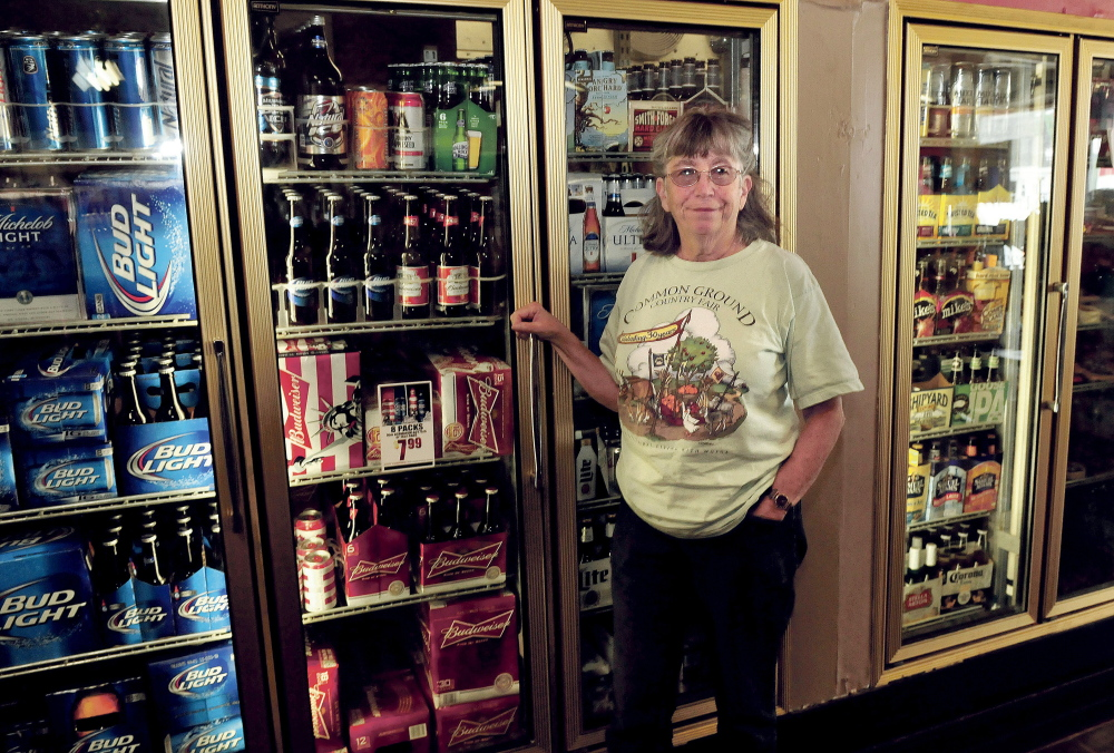 Patty Dowse, owner of the Cambridge General Store, in August, stands beside the beer cooler. Dowse started a petition drive that would allow the store to sell wine on days other than Sunday, reversing a town ordinance.