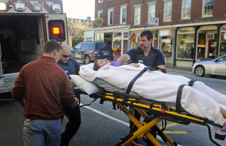Medics wheel a man with stab wounds into an ambulance on Water Street in Hallowell on Monday after he collapsed in the entrance of Dom's Barber Shop.