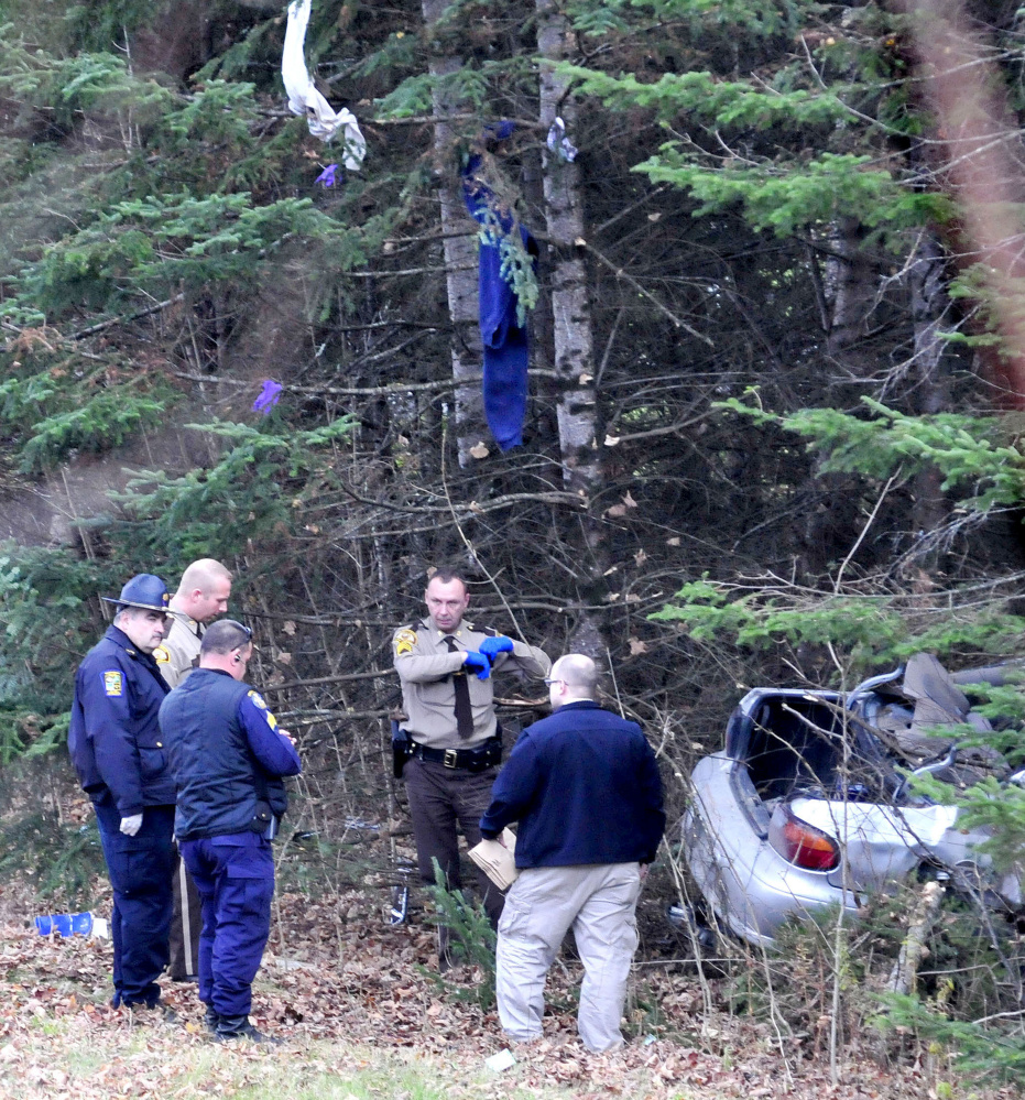 Items from the car driven by Robert Tucker went airborne and hang from trees as police collect evidence from the wreckage of Taylor's car that crashed into trees off the Huff Road in Cornville during a police chase on Monday.