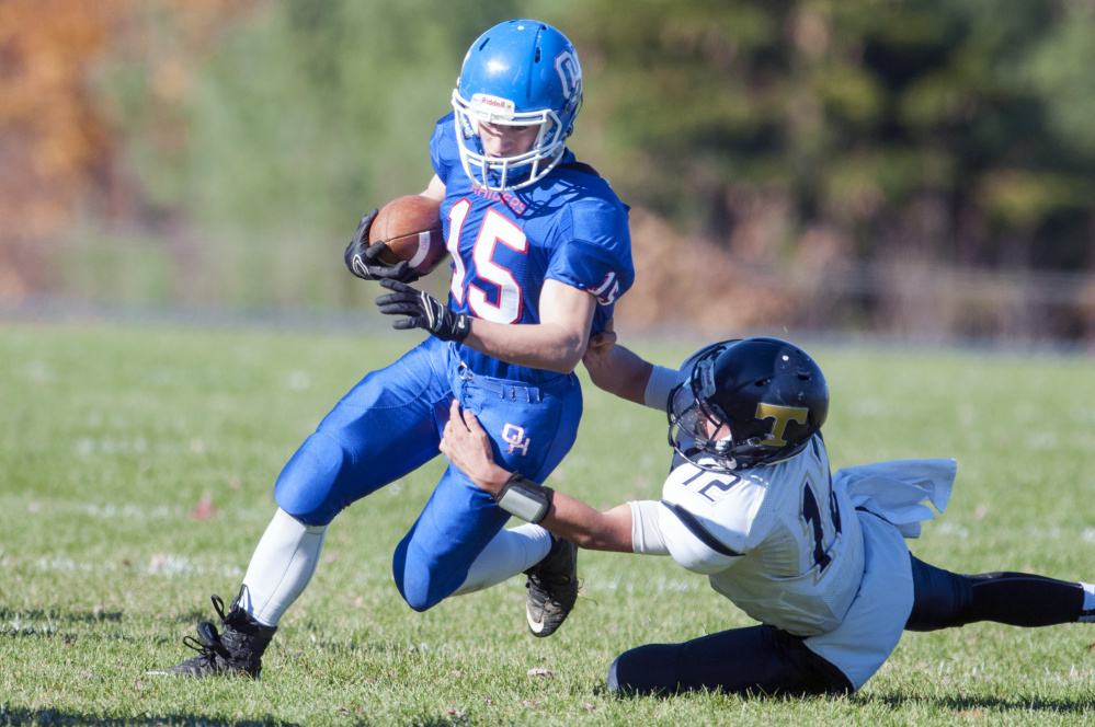 Staff file photo by Joe Phelan   Oak Hill running back Steve Gilbert, left, gets dragged down by Traip defensive back Angelo Succi during a Class D South quarterfinal Saturday afternoon. The Raiders won 48-6 and will next host Winthrop/Monmouth in the semifinals this Saturday.