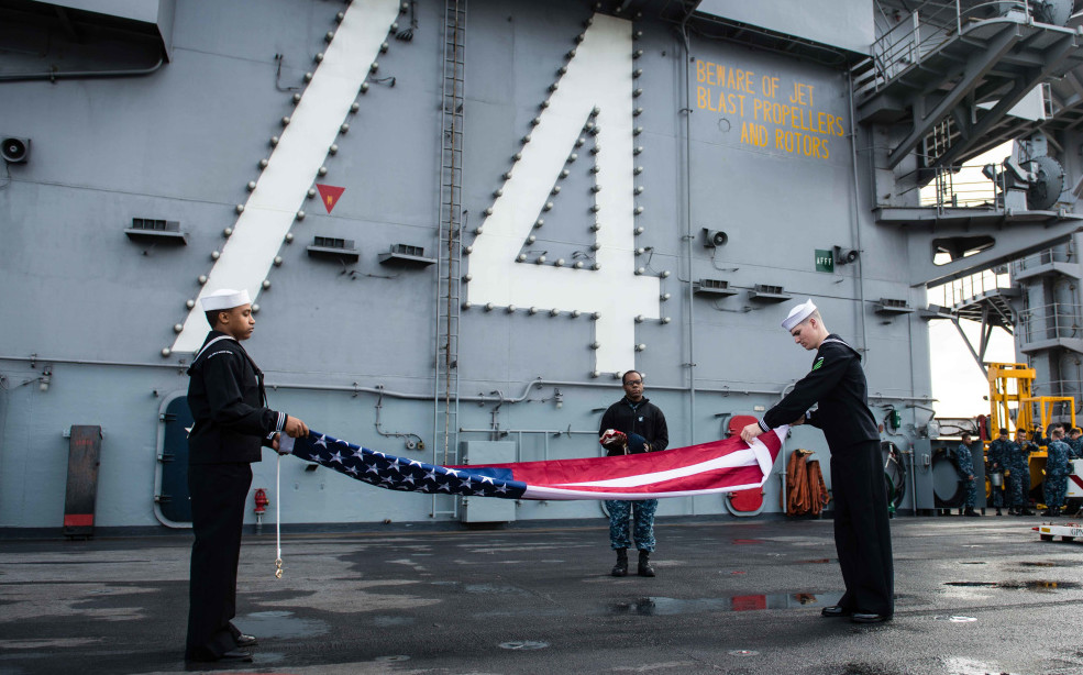 Aviation Boatswain's Mate (hHandling) Jeffrey Brann, of Wilton, and Airman James Anderson, of Cumming, Ga., fold the ensign on the flight deck after USS John C. Stennis (CVN 74) gets underway in the Pacific Ocean, according to a news release from Navy Hometown News. Stennis' crew is currently preparing for fleet replacement squadron carrier qualifications and sustainment exercise.