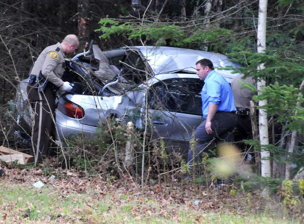 Somerset, state and Skowhegan police remove evidence from the wreckage of the car that Robert Tucker was driving during a police chase that started in Skowhegan and ended when the car left Huff Road in Cornville and crashed into trees on Monday.