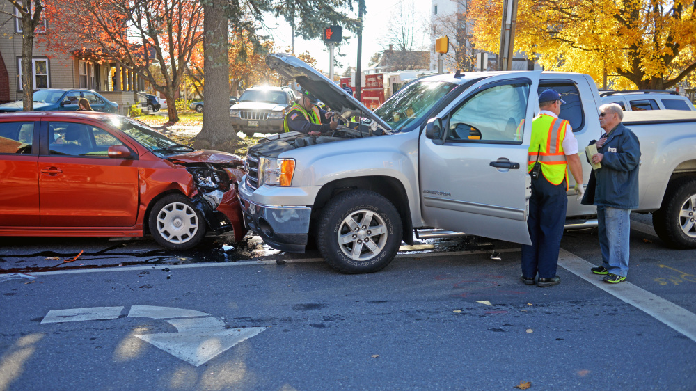 A Delta Ambulance paramedic helps a man involved in a three-car collision at the intersection of Elm and Appleton streets in front of the Waterville Public Library on Wednesday.
