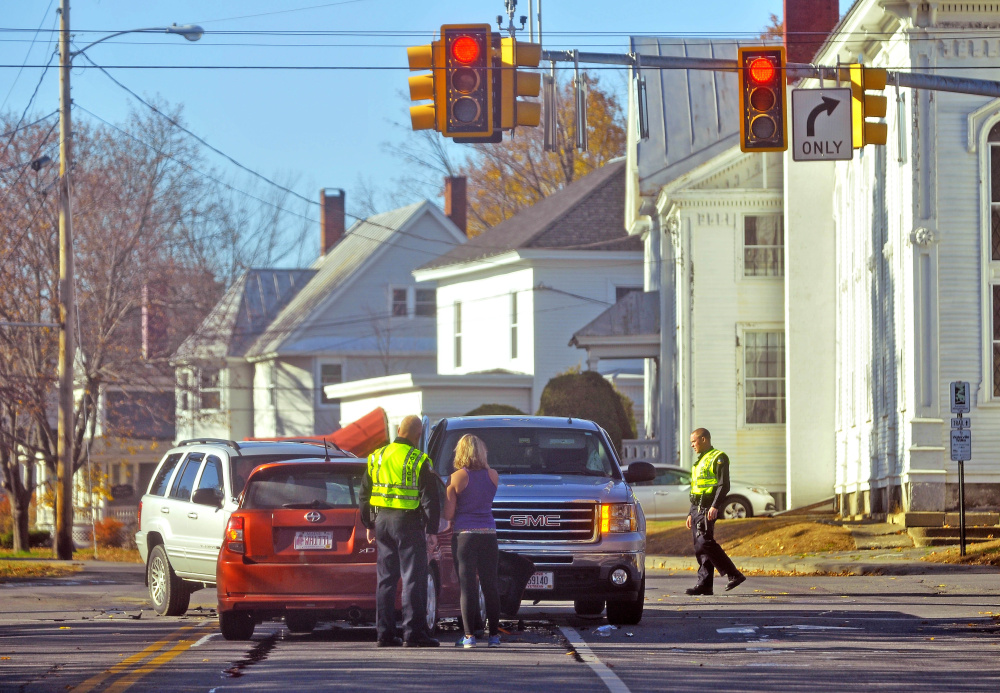 Whitney Blanchet, right, speaks with a Waterville police officer next to her car at the intersection of Elm and Appleton streets in front of the Waterville Public Library on Wednesday.