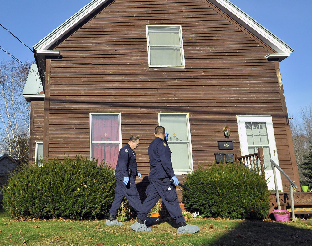 Maine State Police investigators on Thursday search the front of 41 Belgrade Road in Oakland, where three people were killed and the gunman killed himself.
