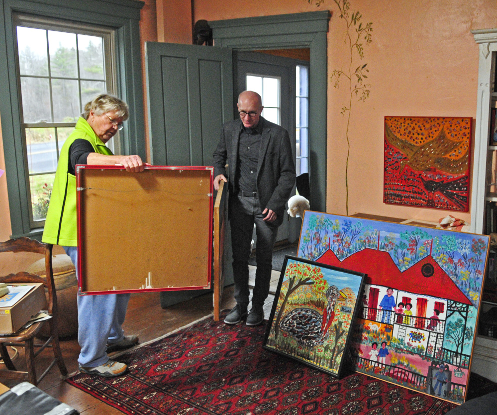 Barbara Skapa, left, and Kent Shankle, executive director of the Waterloo Center For The Arts, look at Haitian paintings on Friday at Skapa's Mount Vernon home. Skapa collected several paintings by Gerard Fortune when she worked in Haiti.