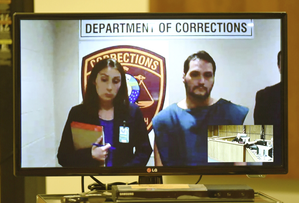 Matthew Dion is arraigned via video in June on double-murder charges at Manchester District Court in Manchester, N.H. Public Defender Aileen O'Connell is pictured at left.