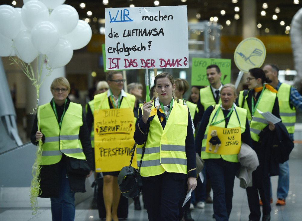 "The Associated Press Lufthansa flight attendants protest at the airport in Duesseldorf, Germany, on Friday. The poster reads ""we make Lufthansa successful – is this the gratitude?"""