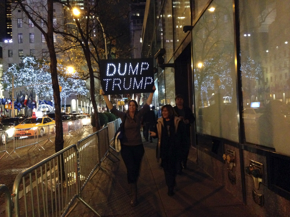"Demonstrators march to protest Donald Trump's views on immigration hours before he hosts ""Saturday Night Live,"" on Saturday. Dozens of protesters held signs and chanted Saturday evening as they marched from Trump Tower to NBC's studio in Rockefeller Plaza."