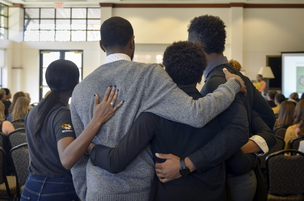 Members of the anti-racism and black awareness group Concerned Student 1950 embrace during a protest in the Reynolds Alumni Center on the University of Missouri campus in Columbia, Missouri, on Saturday.