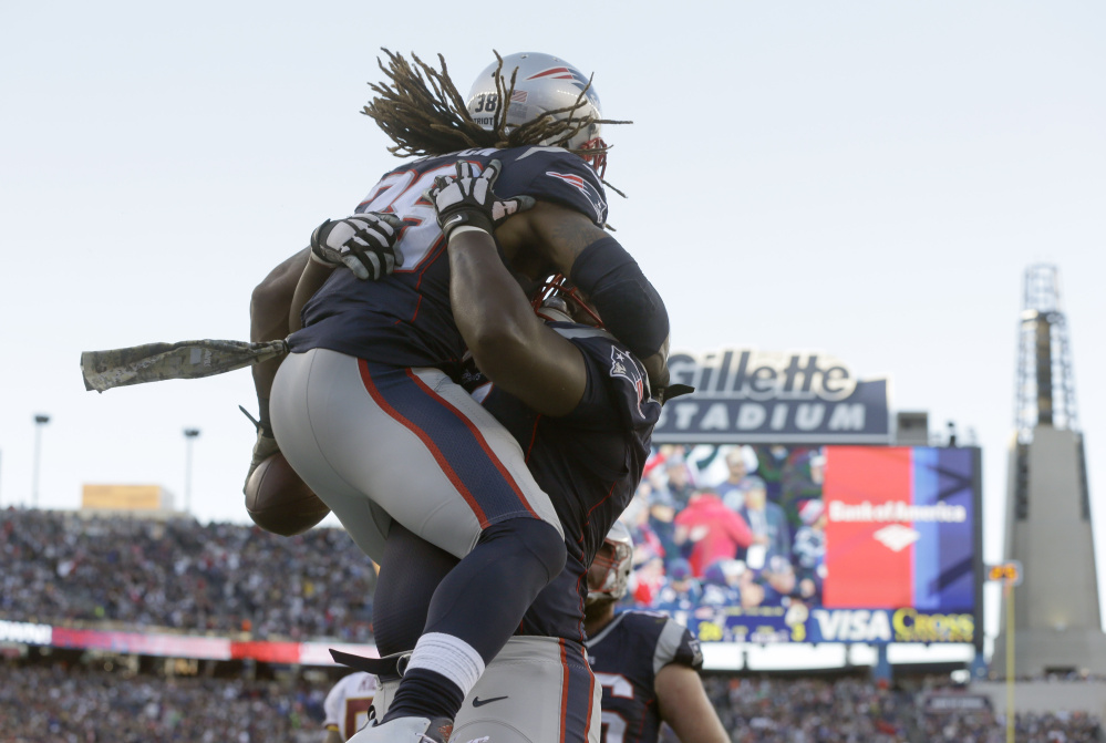 New England Patriots running back Brandon Bolden gets a lift after scoring a touchdown against Washington in the fourth quarter Sunday at  Foxborough, Massachusetts.