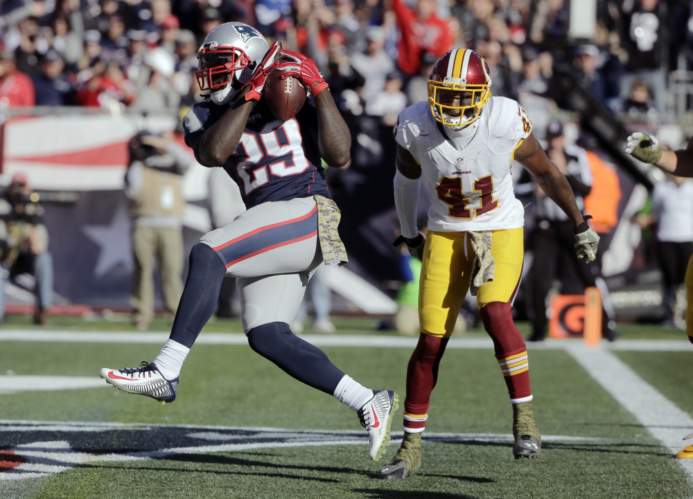 Patriots running back LeGarrette Blount crosses the goal for a first-half touchdown in front of Washington cornerback Will Blackmon on Sunday in Foxborough, Massachusetts.