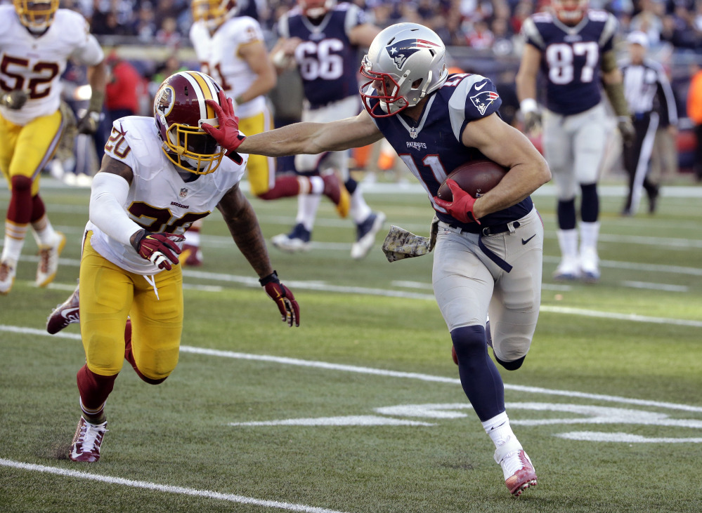 New England Patriots wide receiver Julian Edelman (11) gives a stiff arm to Washington defensive back Jeron Johnson after catching a pass during the second half Sunday in Foxborough, Mass.