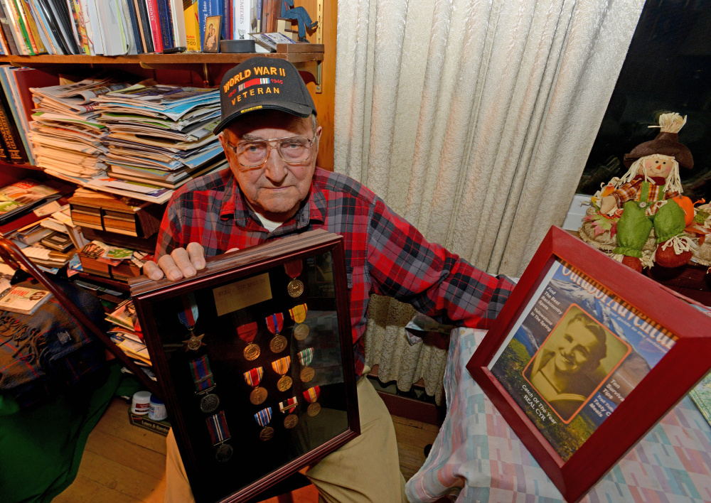 Real Cyr, a World War II veteran, poses with his war medals at his Winslow home on Wednesday.