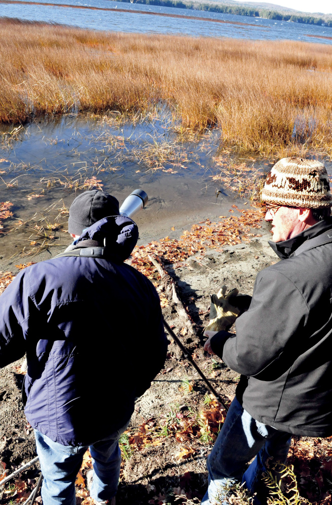 Phil Downes, left, and Louise Bevier prepare to look for waterfowl in the marshy area of North Pond in Smithfield on Sunday.