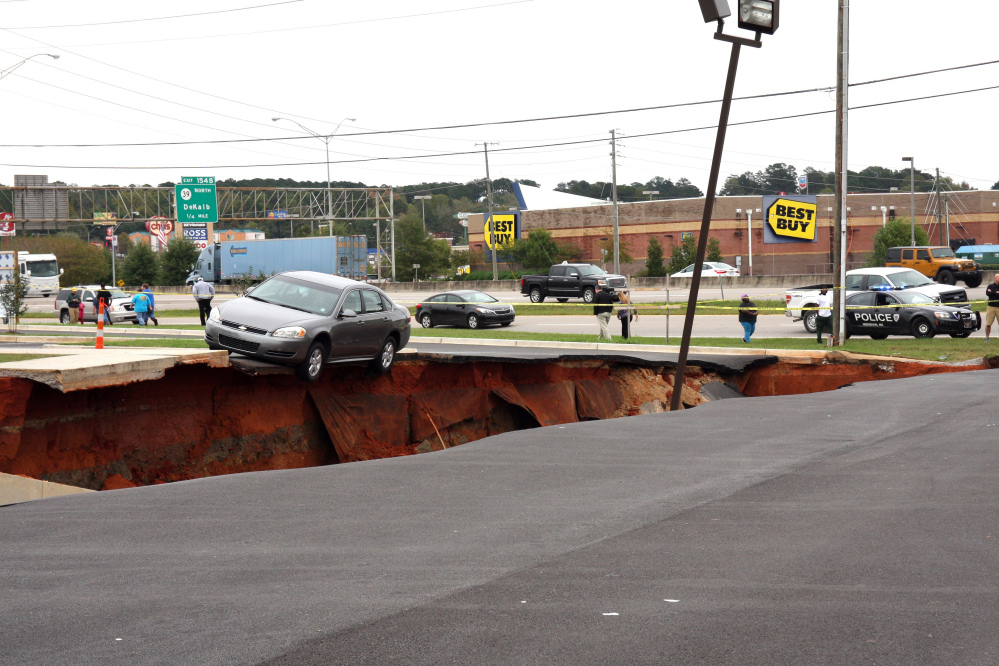 A car teeters on the edge of a cave-in of a parking lot in Meridian, Miss., Sunday.