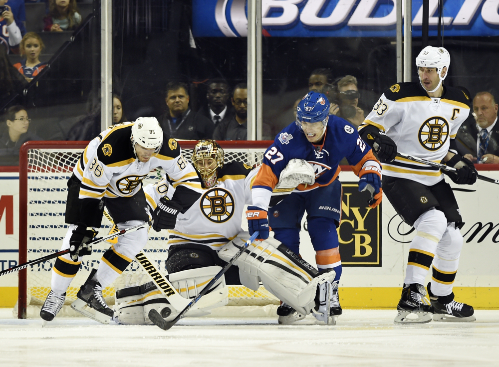 Boston's Kevan Miller (86), goalie Tukka Rask (40) and Zdeno Chara (33) defend against New York Islanders' Anders Lee (27) during the first period Sunday in New York.