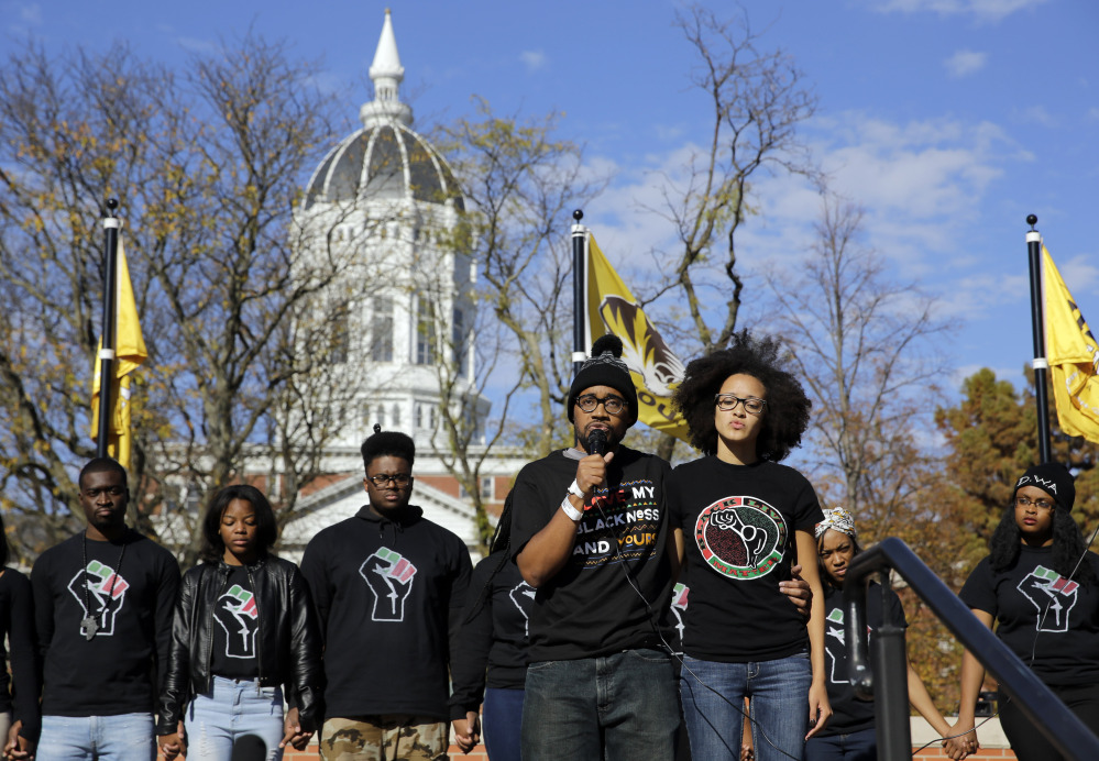 Jonathan Butler, front left, addresses a crowd at the University of Missouri in Columbia after it was announced that university system President Tim Wolfe would resign Monday. Butler ended his hunger strike as a result of the resignation.