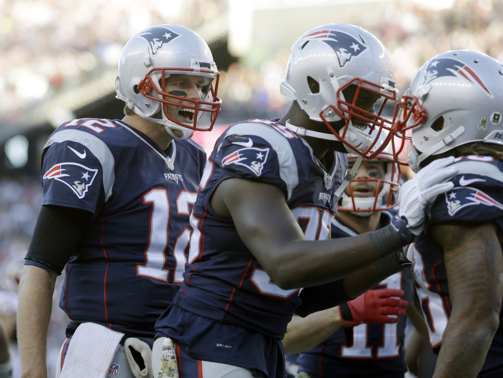 New England Patriots quarterback Tom Brady, left, and defensive end Chandler Jones, center, congratulate running back Brandon Bolden, right, after his touchdown against Washington on Sunday in Foxborough, Mass.