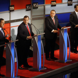 Rick Santorum, left, speaks as Chris Christie, Mike Huckabee and Bobby Jindal listen during Tuesday night's preliminary Republican presidential debate in Milwaukee. The leading candidates in the polls were scheduled to start the main debate at 9 p.m.