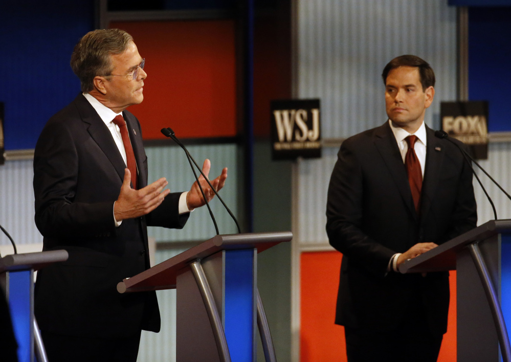 Jeb Bush, left, speaks as Marco Rubio listens during Republican presidential debate at Milwaukee Theatre, Tuesday, Nov. 10, 2015, in Milwaukee. (AP Photo/Morry Gash)