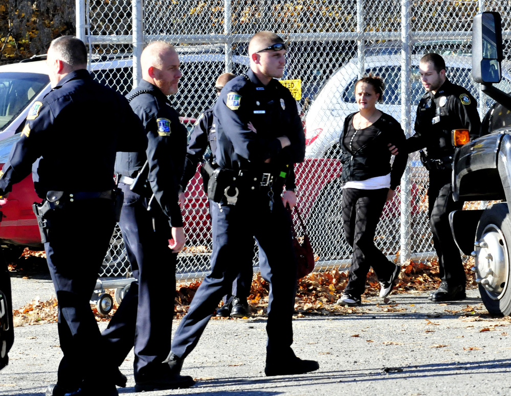 Police officers from Waterville, Winslow and Fairfield are on the scene as Melinda Caven is found hiding behind the Ace Tire store on Drummund Avenue in Waterville on Tuesday. Caven allegedly caused a three-car crash in Fairfield and also hit a house in that town before she was caught up to in Waterville.