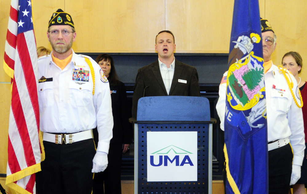 Nathaniel Grace, center, sings the national anthem while flanked by Kennebec County Veterans Honor Guard members Roger Line, left, and Normand Bernier during a veterans' event Tuesday in the Randall Center at the University of Maine at Augusta.