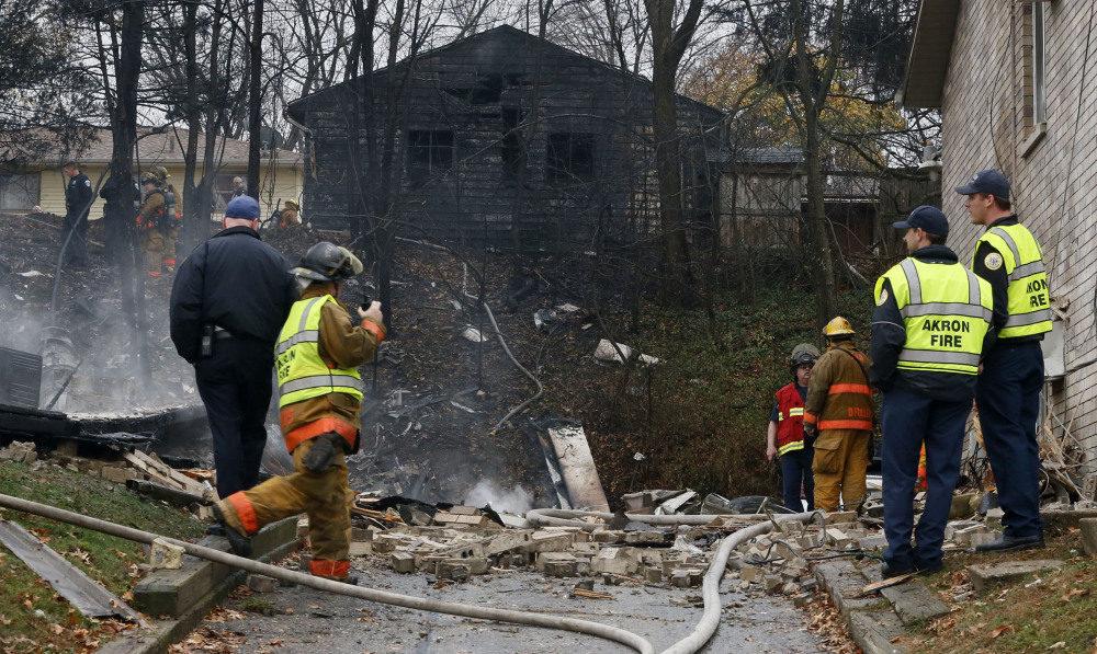 Police and firefighters work at the scene where authorities say a small business jet crashed into an apartment building in Akron, Ohio, Tuesday.