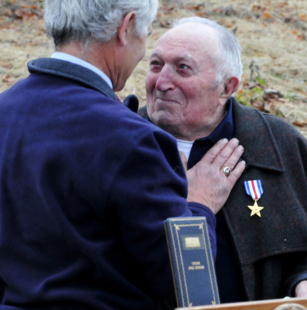 State Sen. Tom Saviello, R-Wilton, left, congratulates Raymond Adams after presenting him with a Silver Star for his duty in World War II at Wednesday's Veterans Day ceremony in Farmington. Adams earned the medal in the war, but never received it.