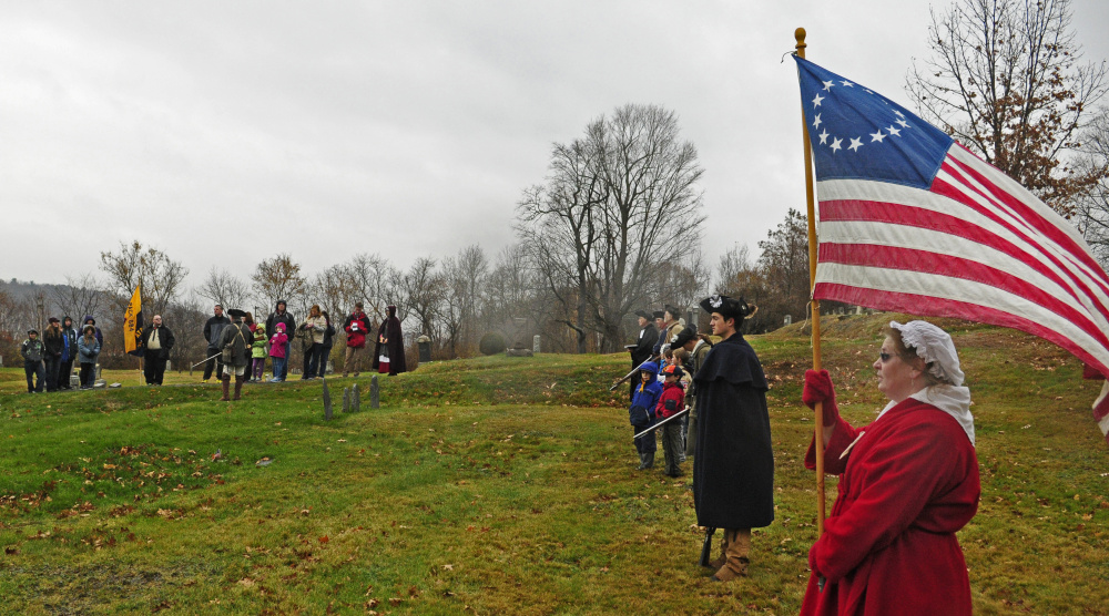 An American flag with 13 stars flies as Cub Scout Pack 684 joins re-enactors at the grave of Revolutionary War soldier Capt. Daniel Savage in Riverside Cemetery during a Veterans Day event on Wednesday in Augusta.