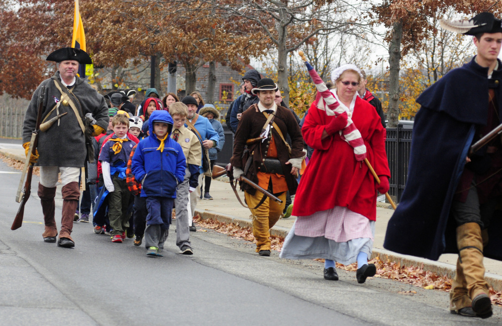 Cub Scout Pack 684 joins re-enactors marching from Old Fort Western to Riverside Cemetery during a Veterans Day event on Wednesday in Augusta.