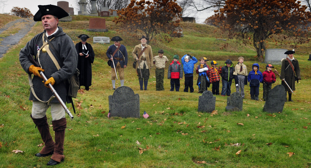 Pete Morrissey, left, speaks to spectators as Cub Scout Pack 684 joins re-enactors at the grave of Revolutionary War soldier Capt. Daniel Savage in Riverside Cemetery during a Veterans Day event on Wednesday in Augusta.