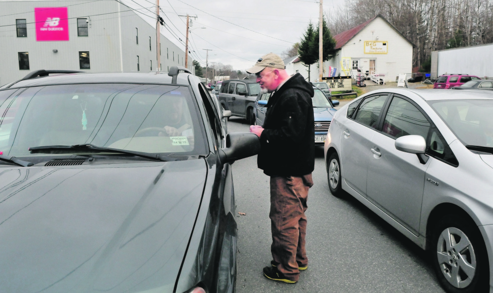 Clark Miller hands out papers with numbers to call to urge the state's congressional delegation to vote against the Trans Pacific Partnership as workers at New Balance in Norridgewock leave for the day Wednesday.